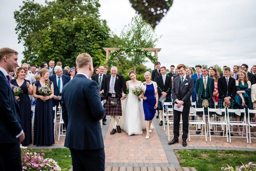 bride walks down aisle at outdoor wedding